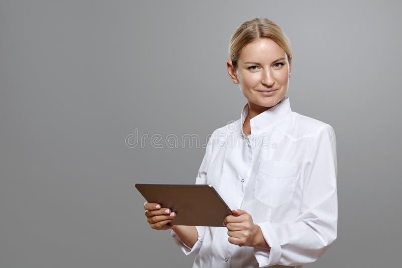 Erba medica sorridente della donna che sta con la compressa fotografie stock