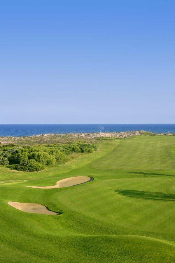 Erba verde di terreno da golf vicino all'oceano del mare fotografia stock