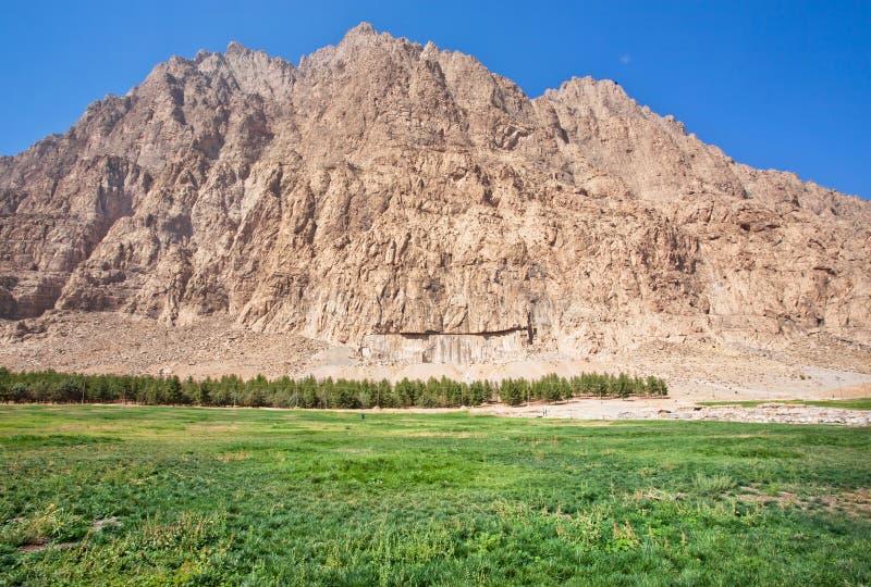 Erba verde nella valle della montagna sotto chiaro cielo blu fotografia stock libera da diritti