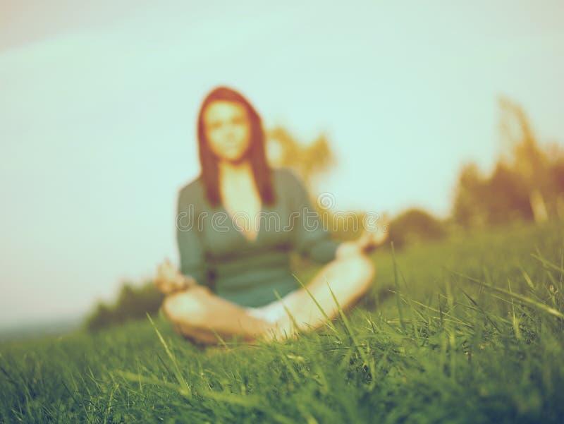 Erba - yoga di pratica della donna nella priorità bassa fotografia stock