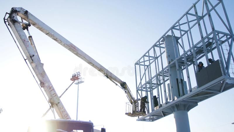 Erbauer auf einer Aufzug-Plattform an einer Baustelle Männer bei der Arbeit zusammenbauendes Gestell des Bauarbeiters auf Baustel stockbild
