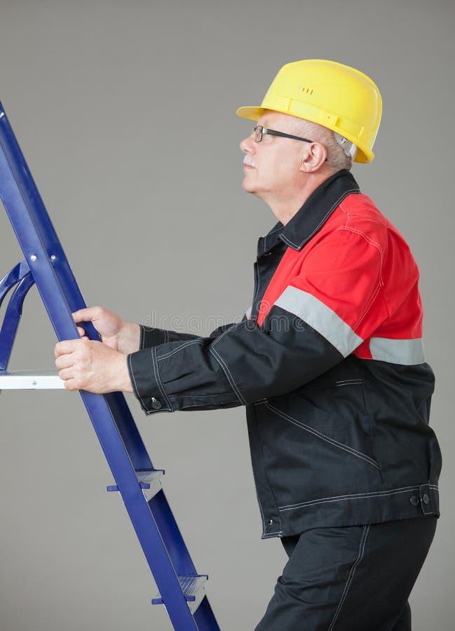 Erbauer, der auf einer Leiter klettert stockfotografie