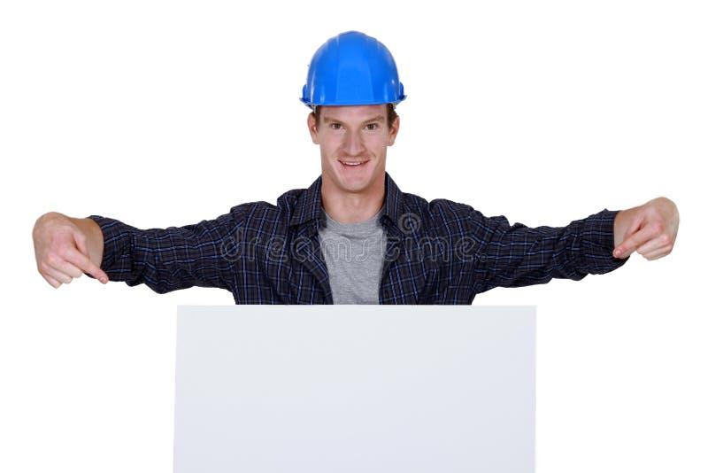 Erbauer, der auf große Anschlagtafel zeigt lizenzfreies stockbild