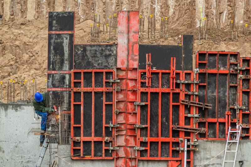 Erbauer, der an Baugrundlage arbeitet Mann in der blauen Arbeitskleidung auf dem bronzierenden Metall der Leiter, zum der Betonma lizenzfreie stockbilder