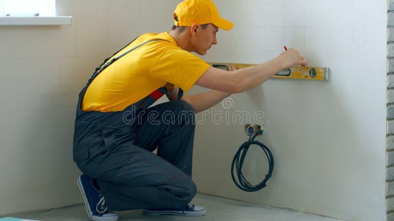 Erbauer, der ein Geistniveau verwendet, um eine Wand zu messen lizenzfreie stockfotografie