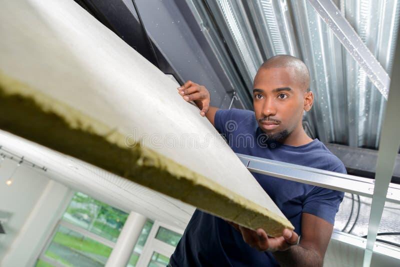 Erbauer, der Isoliermaterial im roofspace hält lizenzfreie stockbilder