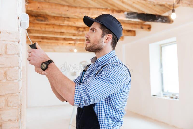 Erbauer, der zuhause mit einer Farbenrolle arbeitet stockfoto