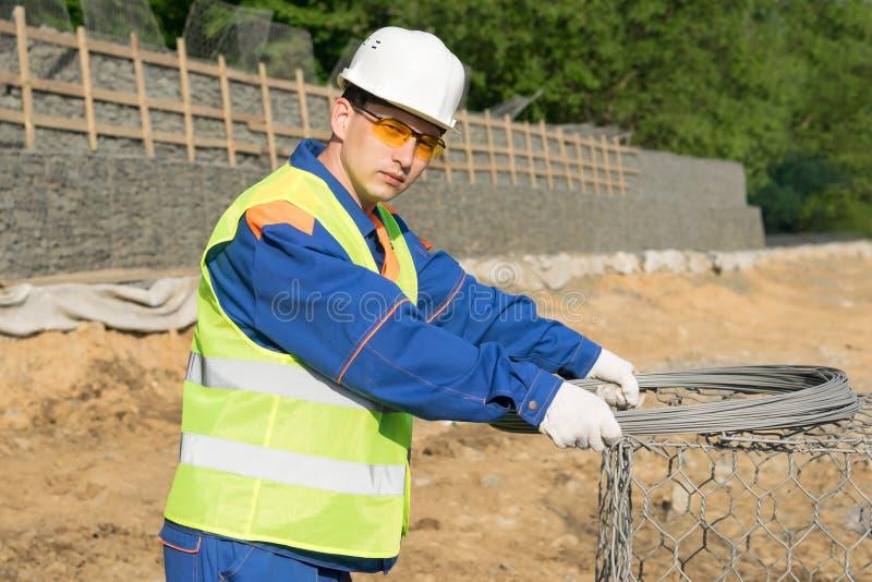 Erbauer in einem Sturzhelm auf dem Hintergrund des Baus, Nahaufnahmeporträt stockfotos