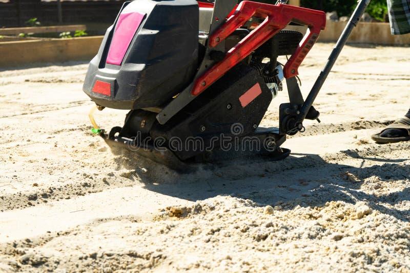 Erbauer mit Vibrationsplatten versiegelt den niedrigen Sand für auslaufenden Beton lizenzfreie stockfotos