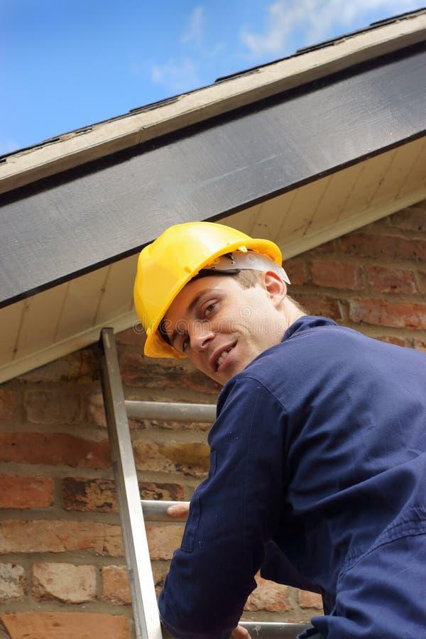Erbauer oder Roofer, die eine Strichleiter steigen lizenzfreies stockfoto