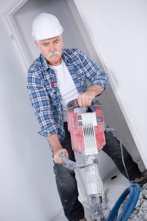 Erbauerarbeitskraft mit pneumatischem Bohrhammer lizenzfreie stockfotografie