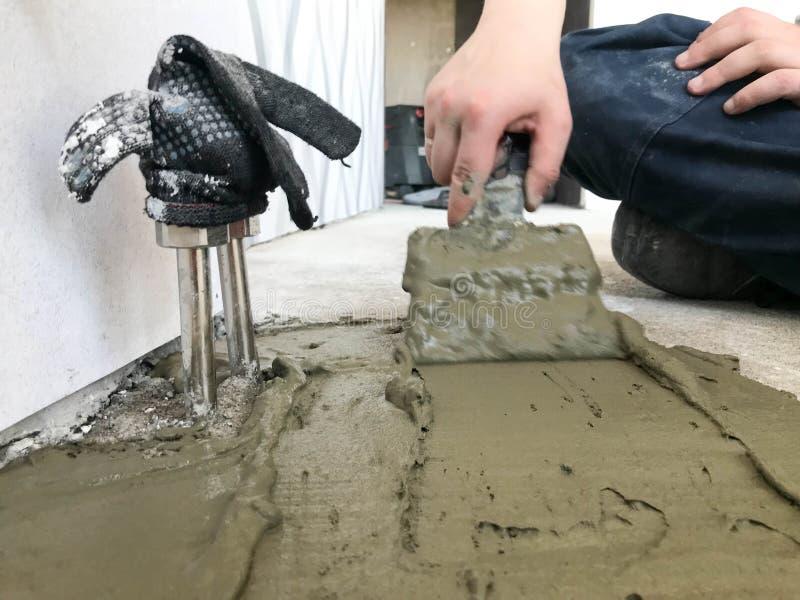 Erbauerhände mit einer Metallspachtel, die Wand zu vergipsen, gießt die Tirade mit Gips, Fliesenkleber, Zement für die Reparatur stockfotografie