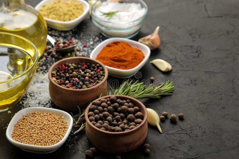 Erbe e spezie vari condimenti, erbe e spezie su un fondo del nero della grafite fotografia stock