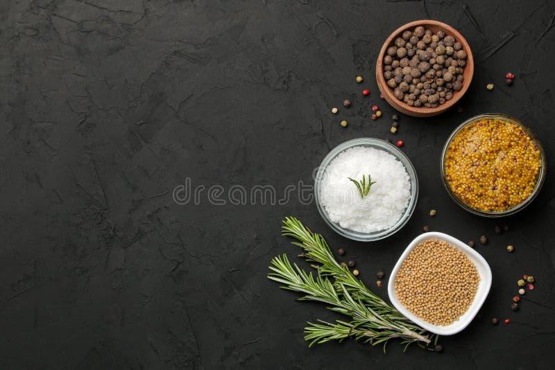 Erbe e spezie vari condimenti, erbe e spezie su un fondo del nero della grafite Vista superiore Posto per testo Spazio libero immagine stock