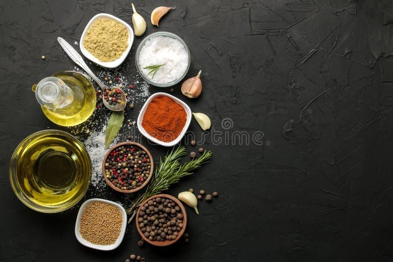 Erbe e spezie vari condimenti, erbe e spezie su un fondo del nero della grafite Vista superiore Posto per testo Spazio libero immagini stock