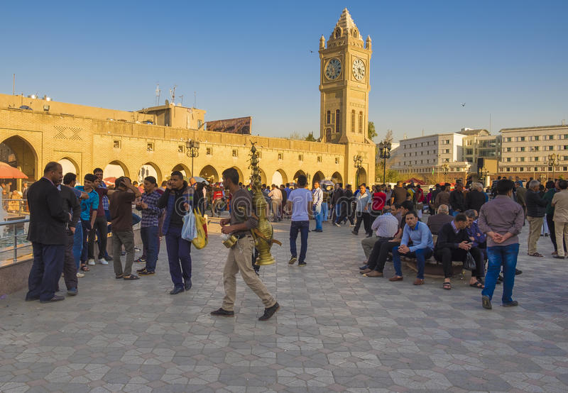 Erbil,Iraq. Erbil, Iraq - March 7, 2016:Old square in Erbil city crowded with people sitting inside and a guy selling licorice juice royalty free stock photography