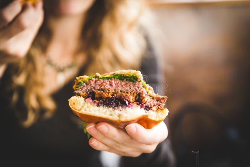Erbjuda en tugga av en läcker hamburgare arkivbild