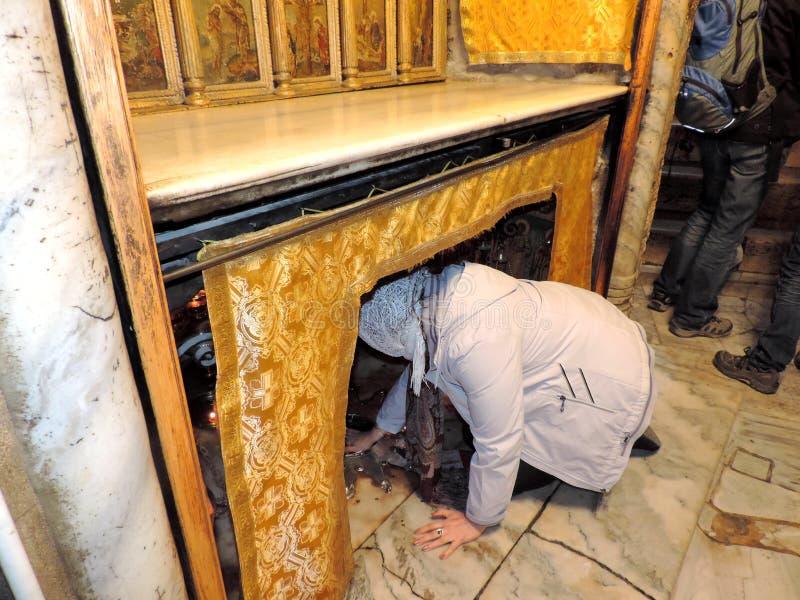 Erbjudande böner för dam på grottan av Kristi födelsen, Betlehem royaltyfri fotografi