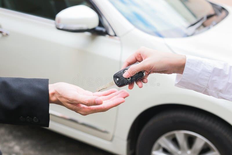 Erbjudande biltangent för representant till en affärsman från bilåterförsäljaren royaltyfri fotografi