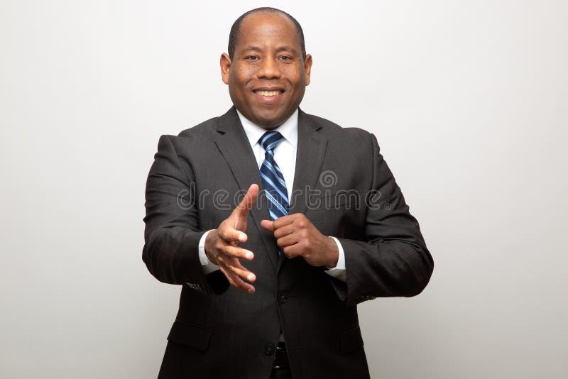 Erbjudande hand för afrikansk amerikanaffärsman för vänlig handskaka royaltyfri fotografi
