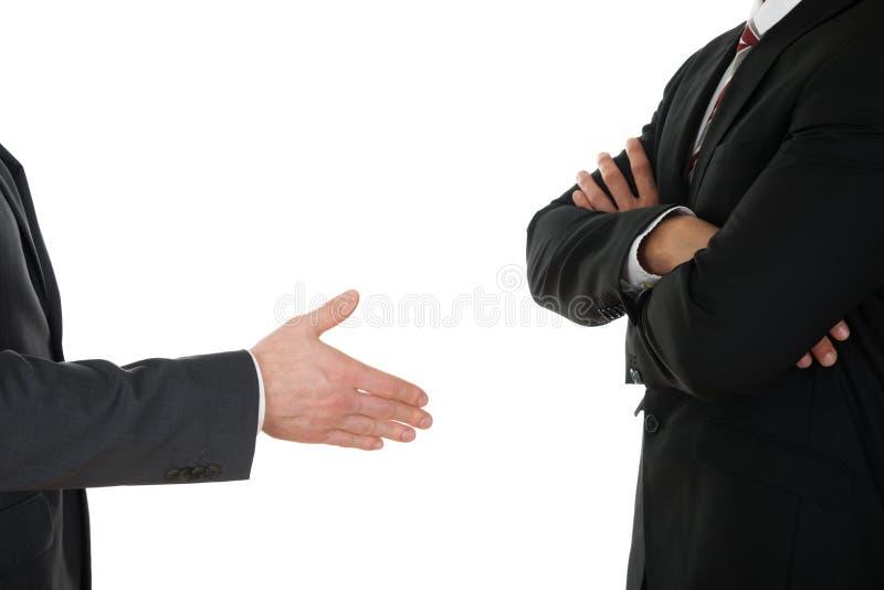 Erbjudande handskakning för person till affärsmannen med den korsade armen royaltyfri bild