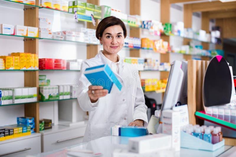 Erbjudande hjälp för kvinnlig apotekare, i att välja på räknaren i pharma arkivfoton