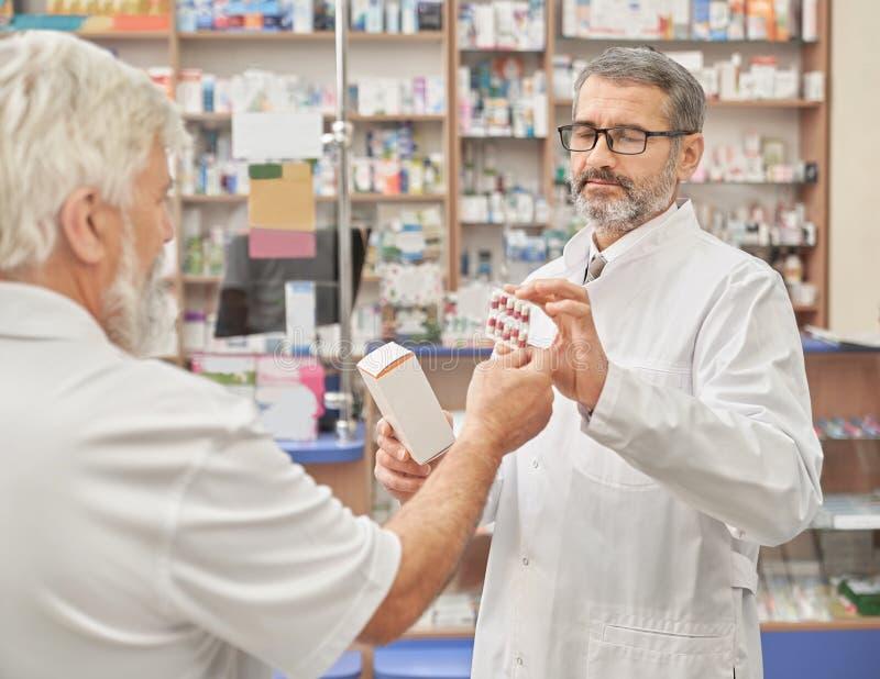 Erbjudande medikament för kemist till den gamla kunden i apotek royaltyfria bilder