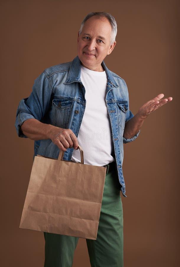 Erbjudande shopping för vänlig man med påsen och att le för papper arkivfoto