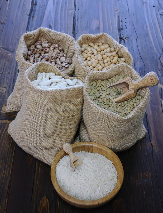 Erbsen in den Textiltaschen und weißer Reis in der Schüssel lizenzfreie stockfotos