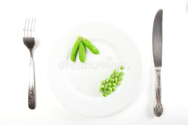 Erbsen mit Hülsen auf einer Platte mit Messer und der Gabel lokalisiert auf weißem Hintergrund stockfotos
