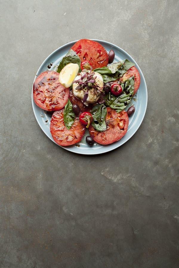 Erbstück-Tomate und burrata Salat überzogen geschmückt mit Basilikum lizenzfreie stockfotografie