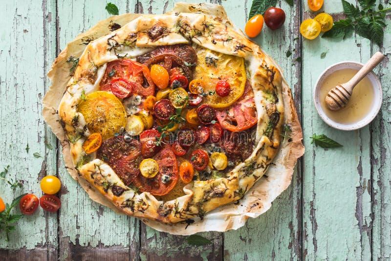 Erbstück-Tomaten scharf mit Zucchini, Blauschimmelkäse, Thymian und Honig stockbild