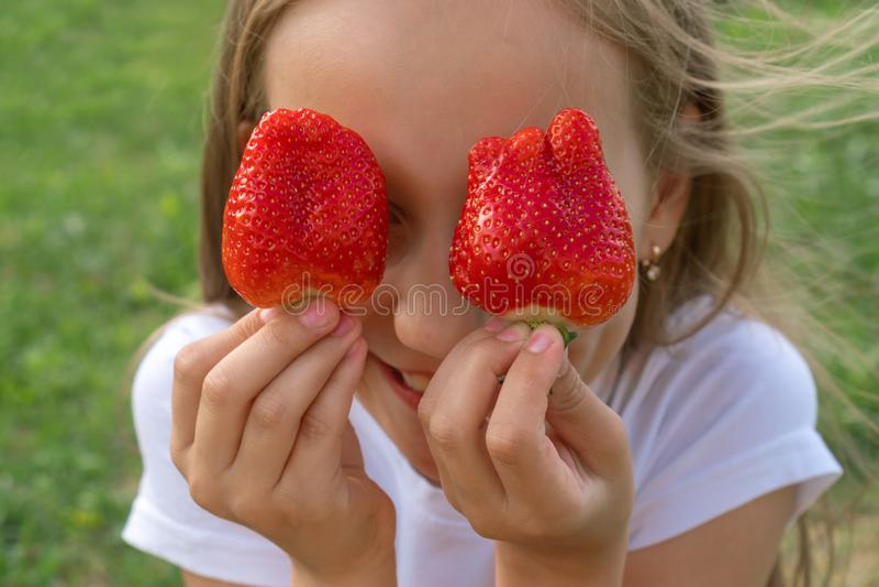 Erdbeeraugen Sch?nes junges M?dchen, das Erdbeeren in den Augen wie Ferngl?sern im Garten h?lt Gesund, Lebensstilkonzept stockfotografie
