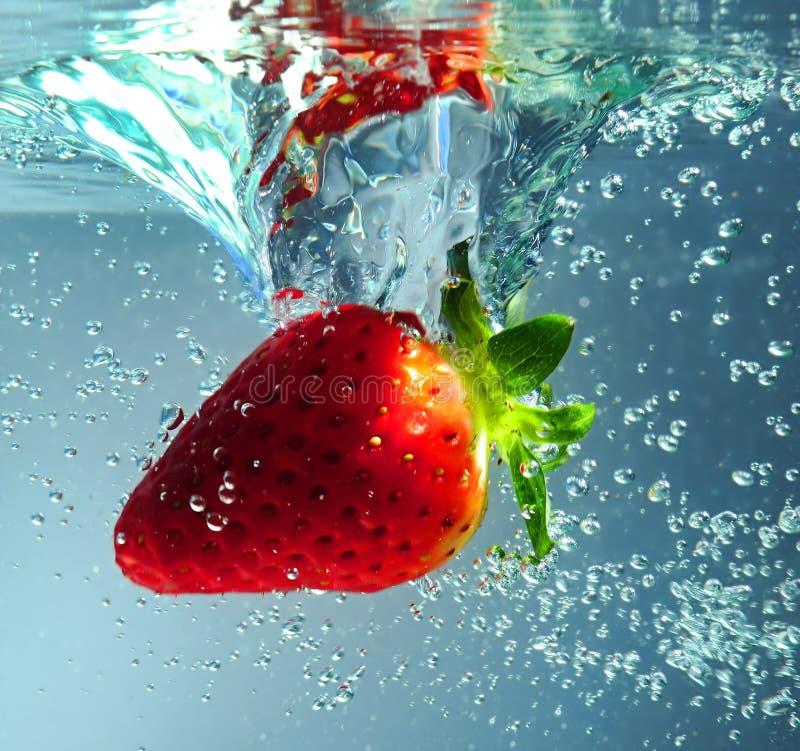 Erdbeere, die im Wasser spritzt stockbild