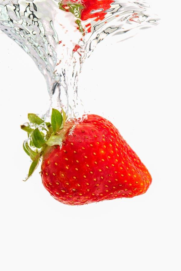 Erdbeere, die unter Wasser mit den Luftblasen lokalisiert auf weißem Hintergrund sinkt stockfotografie