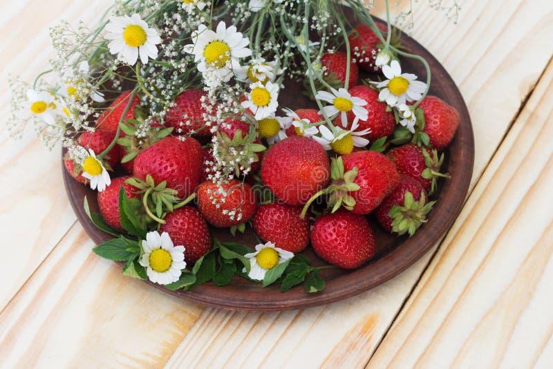 Erdbeere in einer Lehmschale des Blumen Gypsophila-Gänseblümchenfeldes auf einer Holztischnahaufnahme stockfoto
