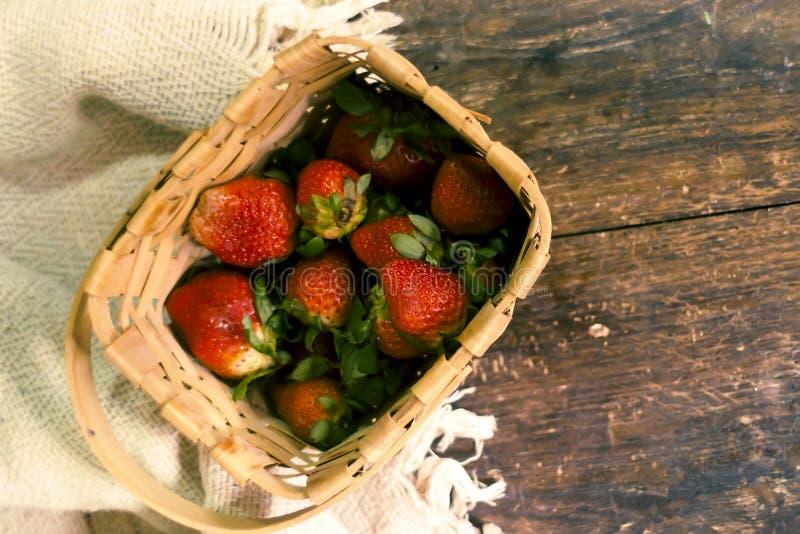 Erdbeere in gesponnenem Korb Frische Erdbeere Rote Erdbeere Erdbeersaft H?lzerner Tabellenhintergrund lizenzfreies stockbild