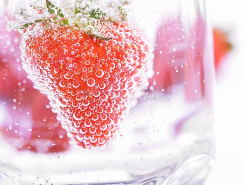 Erdbeere im Mineralwasser mit boobles lizenzfreies stockbild