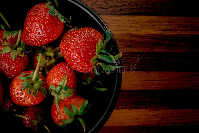 Erdbeere im Schüsselschwarzen lizenzfreie stockbilder