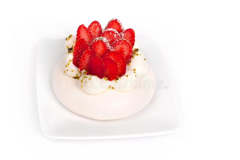 Erdbeere-Pavlova-Kuchen auf wei?er Platte auf einem wei?en Hintergrund nah oben lokalisiert lizenzfreies stockbild