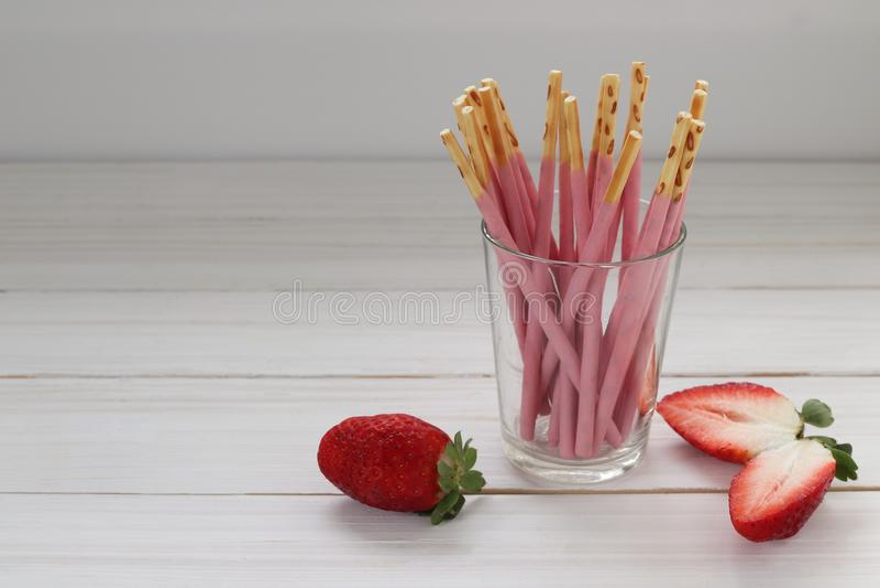 Erdbeere tauchte Keksstöcke im Glashalter ein stockfoto