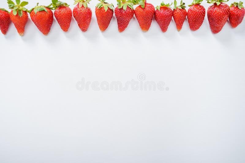 Erdbeere trägt in Folge auf weißem hölzernem Tabellenhintergrund Früchte stockbilder