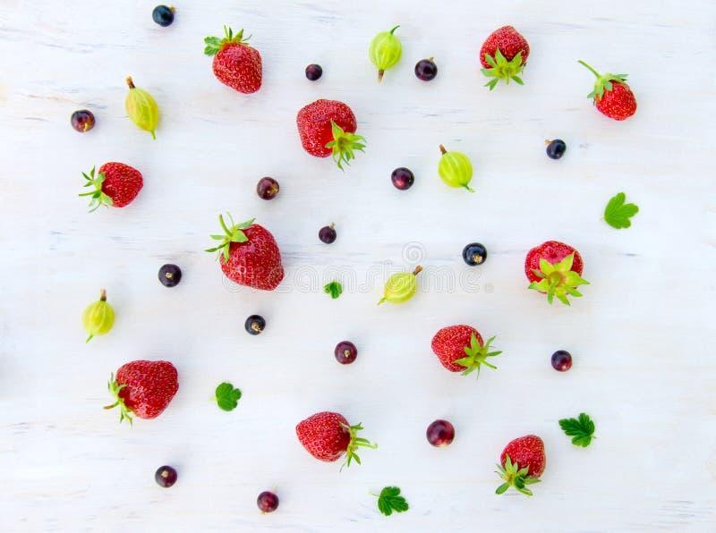 Erdbeere und Stachelbeerbeeren und -korinthen ausgebreitet auf einem hölzernen weißen Hintergrund lizenzfreie stockfotografie