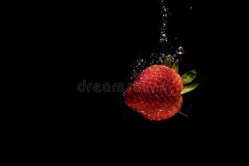 Erdbeere versenkt in das Wasser umgeben durch Blasen stockfotografie