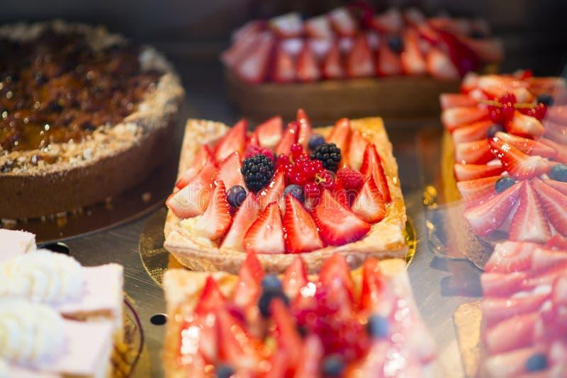Erdbeeren backen oder Tartlets im Konditoreiregal zusammen lizenzfreies stockfoto