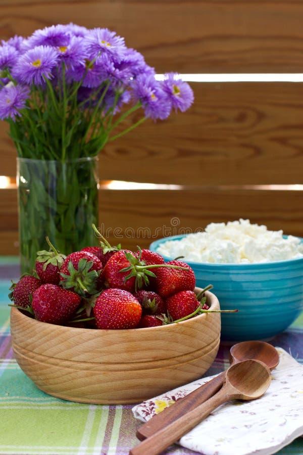 Erdbeeren in der hölzernen Schüssel und im Hüttenkäse stockfotos