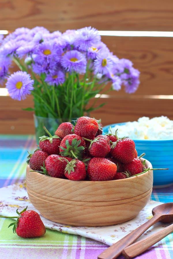Erdbeeren in der hölzernen Schüssel und im Hüttenkäse lizenzfreie stockfotos