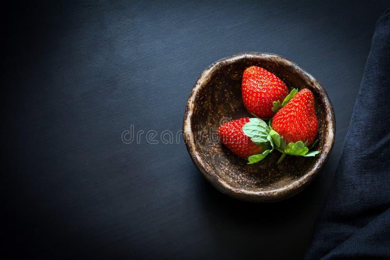 Erdbeeren in der Schüssel auf schwarzem Hintergrund, Tischplatteansicht lizenzfreies stockbild