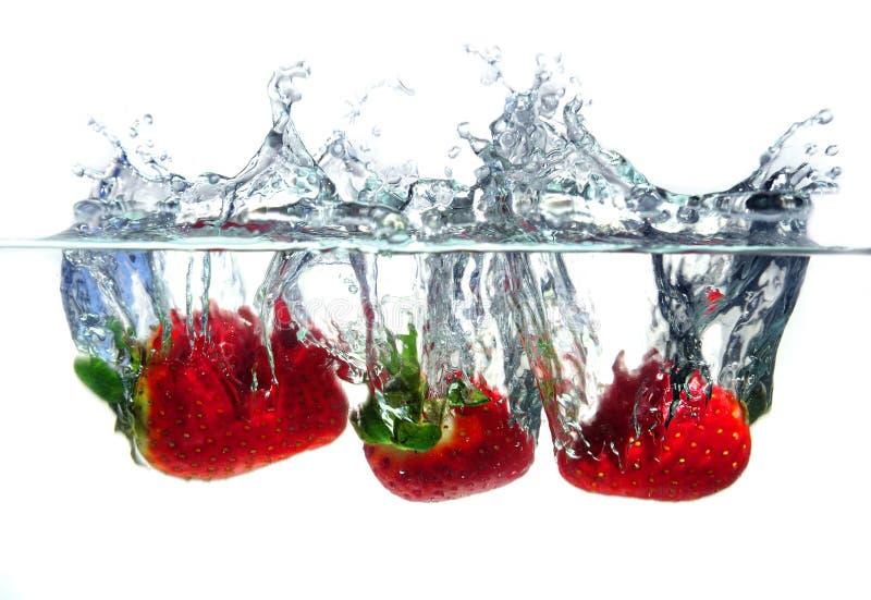 Erdbeeren, die in Wasser fallen stockfotos