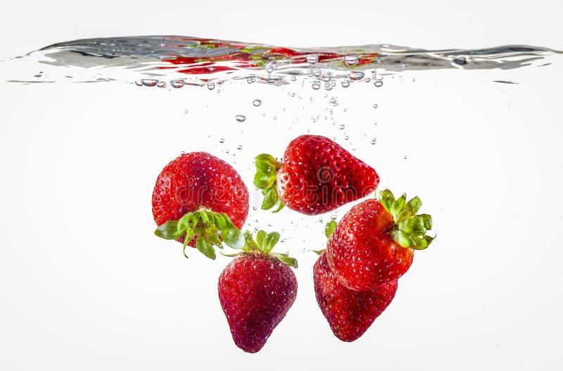 Erdbeeren, die in Wasser schwimmen stockfoto